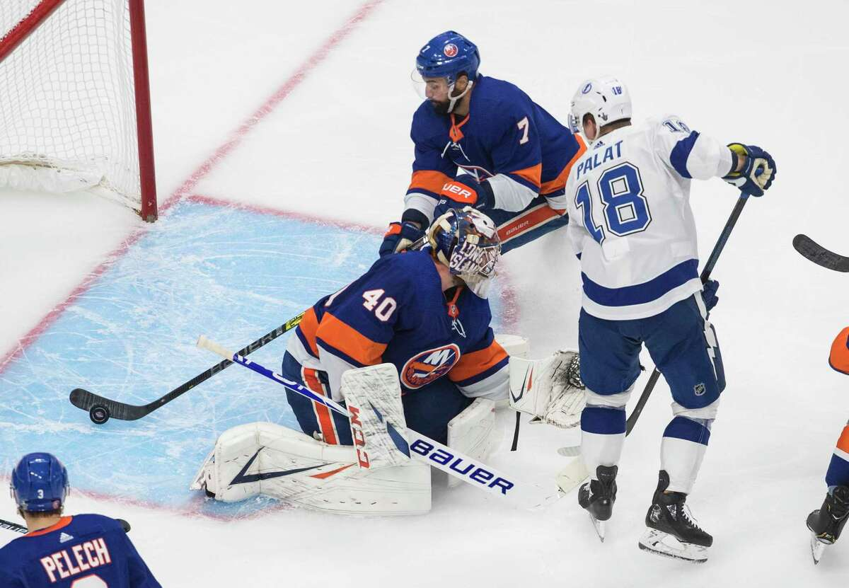 Tampa Bay Lightning's Ondrej Palat (18) gets the puck past New York Islanders goalie Semyon Varlamov (40) as Jordan Eberle (7) picks it up before it crosses the line during the third period of an NHL Eastern Conference final playoff game in Edmonton, Alberta, on Sunday, Sept. 13, 2020. (Jason Franson/The Canadian Press via AP)