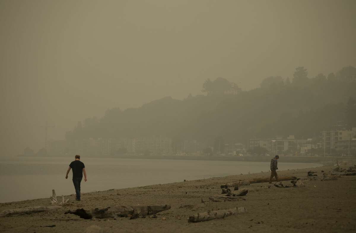 SEATTLE, WA - SEPTEMBER 12: People walk on the sand as smoke from wildfires fills the air at Alki Beach Park on September 12, 2020 in Seattle, Washington. According to the National Weather Service, the air quality in Seattle remained at