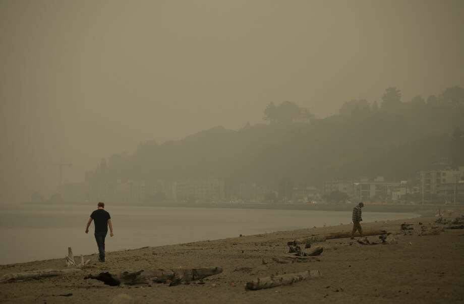 "SEATTLE, WA - SEPTEMBER 12: People walk on the sand as smoke from wildfires fills the air at Alki Beach Park on September 12, 2020 in Seattle, Washington. According to the National Weather Service, the air quality in Seattle remained at ""unhealthy"" levels Saturday after a large smoke cloud from wildfires on the West Coast settled over the area. (Photo by Lindsey Wasson/Getty Images) Photo: Lindsey Wasson/Getty Images / 2020 Getty Images"