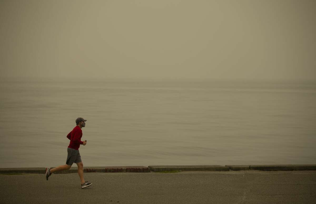 SEATTLE, WA - SEPTEMBER 12: A man jogs as smoke from wildfires fills the air at Alki Beach Park on September 12, 2020 in Seattle, Washington. According to the National Weather Service, the air quality in Seattle remained at