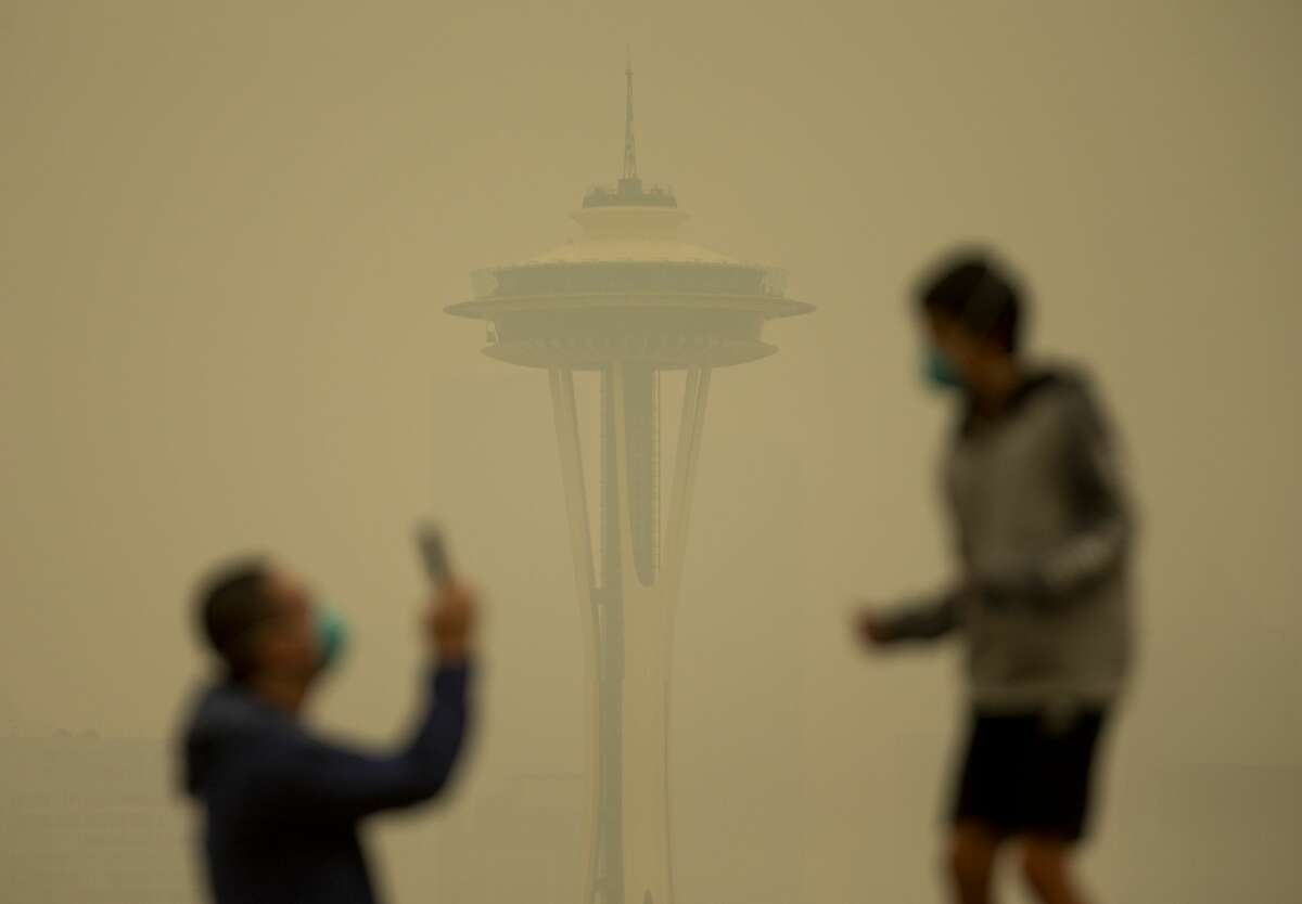 SEATTLE, WA - SEPTEMBER 12: People take photos against the backdrop of the Space Needle as smoke from wildfires fills the air at Kerry Park on September 12, 2020 in Seattle, Washington. According to the National Weather Service, the air quality in Seattle remained at