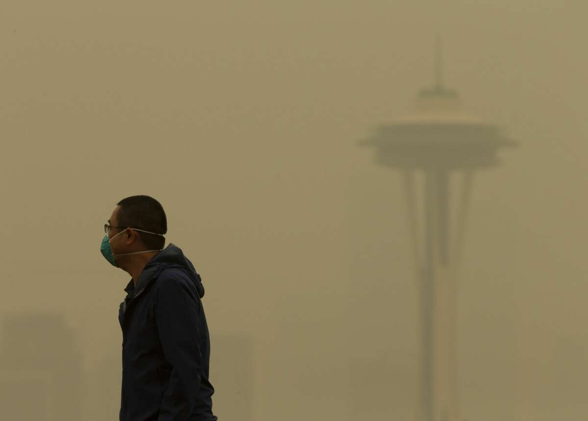SEATTLE, WA - SEPTEMBER 12: A man wearing a mask walks along Kerry Park as smoke from wildfires fills the air on September 12, 2020 in Seattle, Washington. According to the National Weather Service, the air quality in Seattle remained at