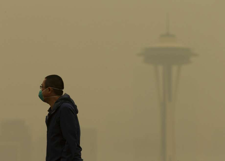 """SEATTLE, WA - SEPTEMBER 12: A man wearing a mask walks along Kerry Park as smoke from wildfires fills the air on September 12, 2020 in Seattle, Washington. According to the National Weather Service, the air quality in Seattle remained at """"unhealthy"""" levels Saturday after a large smoke cloud from wildfires on the West Coast settled over the area. (Photo by Lindsey Wasson/Getty Images) Photo: Lindsey Wasson/Getty Images / 2020 Getty Images"""