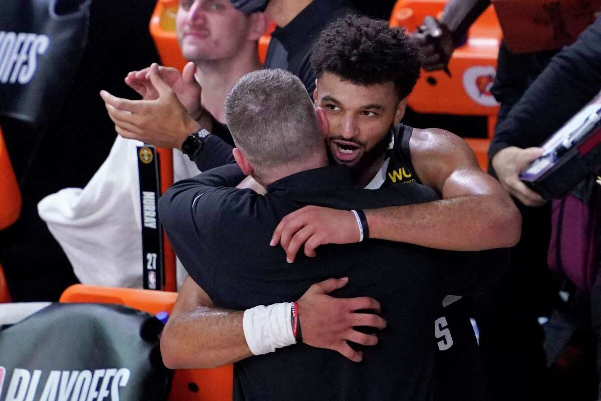 Denver Nuggets coach Michael Malone, left, and Jamal Murray hug after an NBA conference semifinal playoff basketball game against the Los Angeles Clippers Sunday, Sept. 13, 2020, in Lake Buena Vista, Fla. The Nuggets won 111-98. (AP Photo/Mark J. Terrill)