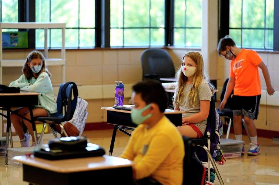 Estudiantes de quinto grado portan mascarillas en espera de su maestro en el aula en la Escuela Primaria Oak Terrace en Highwood, Illinois, parte del distrito escolar de North Shore. Photo: Nam Y. Huh /Associated Press / Copyright 2020 The Associated Press. All rights reserved.