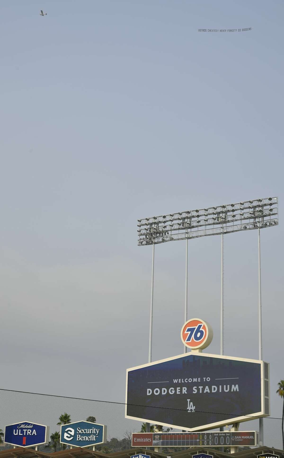LOS ANGELES, CA - SEPTEMBER 13: A small aircraft towing a banner flies over Dodger Stadium while the Houston Astros take batting practice before playing the Los Angeles Dodgers at Dodger Stadium on September 13, 2020 in Los Angeles, California. (Photo by John McCoy/Getty Images)