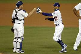 Los Angeles Dodgers catcher Will Smith, left, celebrates with right fielder Mookie Betts after the Dodgers defeat the Houston Astros 8-1 in a baseball game in Los Angeles, Sunday, Sept. 13, 2020. (AP Photo/Alex Gallardo)
