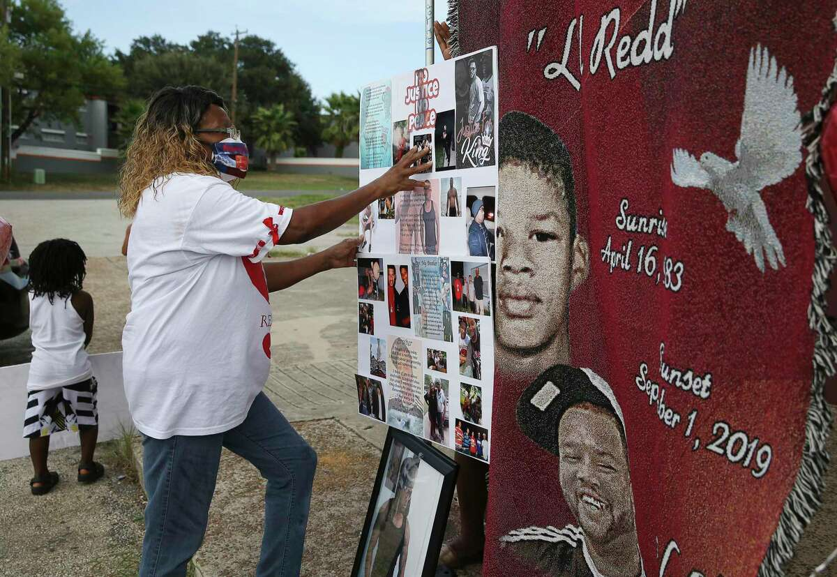 Kathy Clark Robinson puts up a poster of photos as she and other family members of Anthony Clark spend time at the spot where he was shot and killed outside the Groove nightclub on Monday, Sept. 7, 2020. Clark's mother, Barbara Boyd, still mourns the loss of her son as she and other family members held a memorial and balloon release on Monday. Suspects have yet to have been identified since Clark's death at the East Side club.