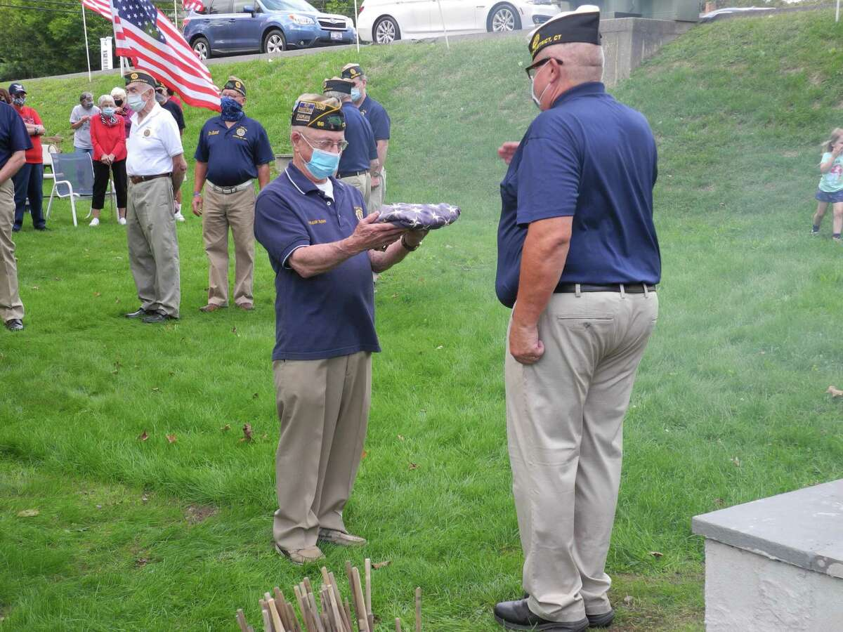 Veteran Frank Dunn presents a flag to Adjutant Tom Moore during the flag retirement ceremony at the American Legion Post 86 on Old Ridgefield Road on Sept. 13, 2020.