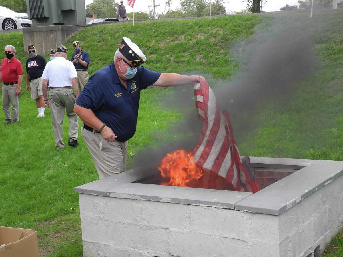Adjutant Tom Moore places a flag in the fire pit during the flag retirement ceremony at the American Legion Post 86 on Old Ridgefield Road on Sept. 13, 2020.