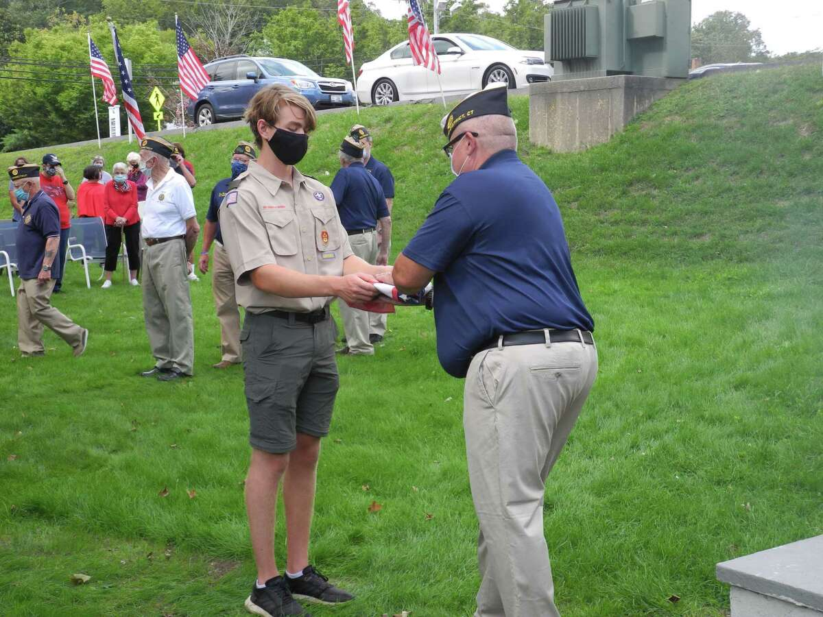 Troop 20 Eagle Scout Ian Kineon presents a flag to Adjutant Tom Moore during the flag retirement ceremony at the American Legion Post 86 on Old Ridgefield Road on Sept. 13, 2020.