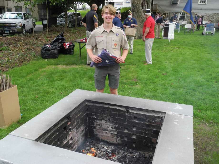 Troop 20 Eagle Scout Ian Kineon holds a flag over the fire pit he built at the American Legion Post 86 on Old Ridgefield Road on Sept. 13, 2020. Photo: Jeannette Ross / Hearst Connecticut Media / Wilton Bulletin