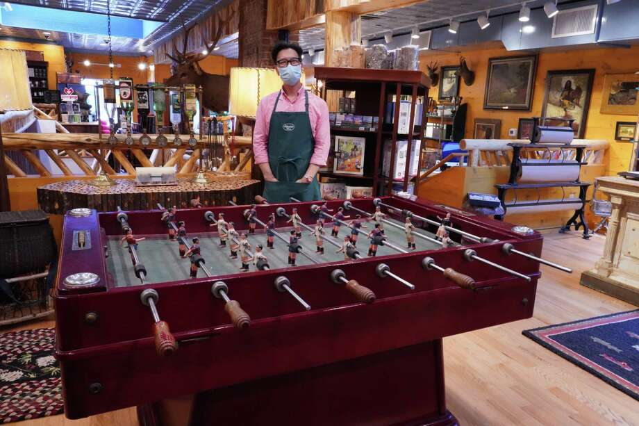 Steve Shin, owner of the Adirondack Store in New Canaan, 39 Elm Street, stands in front of a vintage Spanish Foosball set that was curated by his partner Christopher English. The store offers many other themed items including chaga teas, rugs, glass and modern Old Hickory furniture. Photo: Grace Duffield / Hearst Connecticut Media