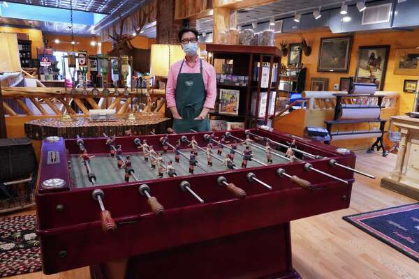 Steve Shin, owner of the Adirondack Store in New Canaan, 39 Elm Street, stands in front of a vintage Spanish Foosball set that was curated by his partner Christopher English. The store offers many other themed items including chaga teas, rugs, glass and modern Old Hickory furniture.