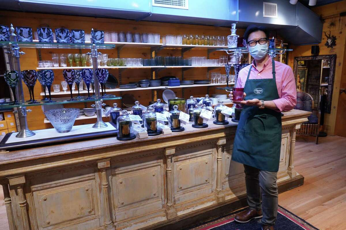 New Canaan resident Steve Shin shows off engraved barnyard-themed engraved glass in the Adirondack Store and Gallery that he owns with Christopher English. He is impressed with the local culture. The shoppers are