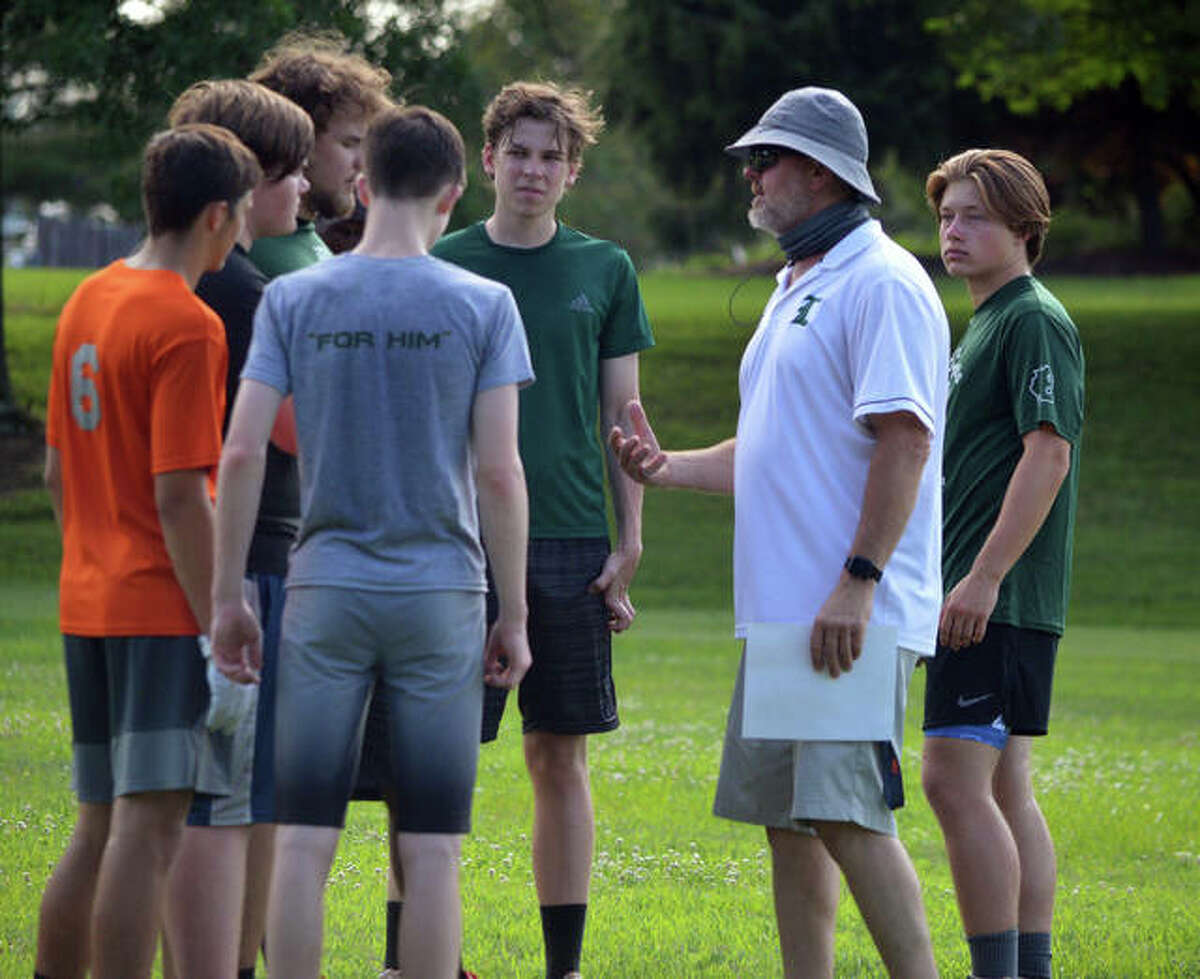 Metro-East Lutheran football coach Bob Keplar, second from right, talks to his players during a summer practice session in July.