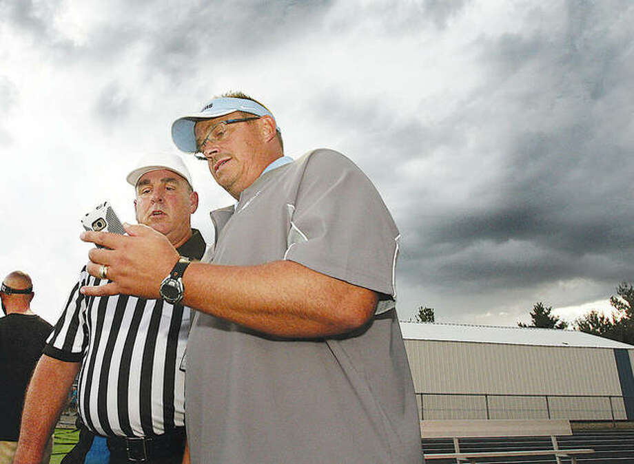 With storm clouds forming behind them, Jersey coach Dave Jacobs and referee Curtis May look at a weather map on Jacobs' phone during a 2014 game that was postponed on a Friday night and played the next day. With prep football enduring a different kind of storm in 2020, a #Let Us Play Rally will be held at 1 p.m. Saturday at the State Capitol in Springfield. Photo: Telegraph File