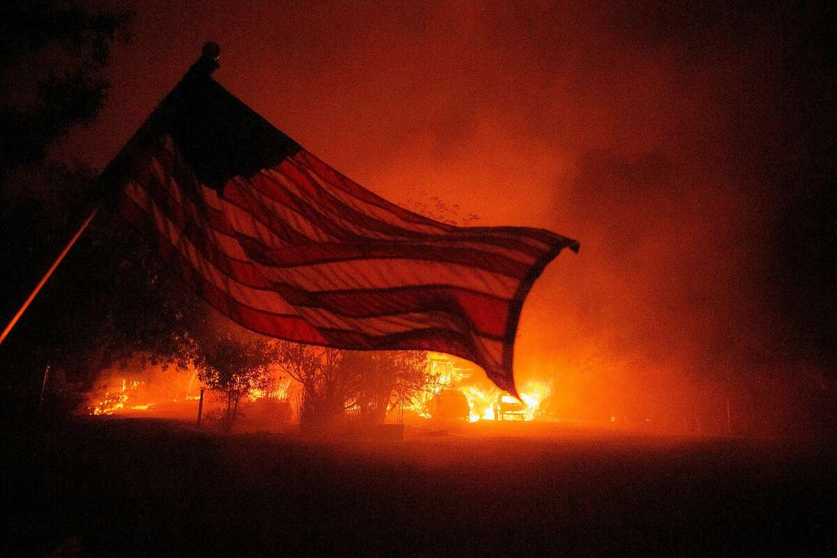 TOPSHOT - An American flag blows in the wind in front of a burning home in Vacaville, California during the LNU Lightning Complex fire on August 19, 2020. - As of the late hours of August 18,2020 the Hennessey fire has merged with at least 7 fires and is now called the LNU Lightning Complex fires. Dozens of fires are burning out of control throughout Northern California as fire resources are spread thin. (Photo by JOSH EDELSON / AFP) (Photo by JOSH EDELSON/AFP via Getty Images)