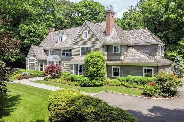 The custom-built colonial house at 52 Charcoal Hill Road sits on a private two-acre property in the Coleytown neighborhood .