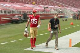 SANTA CLARA, CALIFORNIA - SEPTEMBER 13: George Kittle #85 of the San Francisco 49ers walks off the field with trainer Tim McAdams just before halftime of their game against the Arizona Cardinals at Levi's Stadium on September 13, 2020 in Santa Clara, California. (Photo by Ezra Shaw/Getty Images)