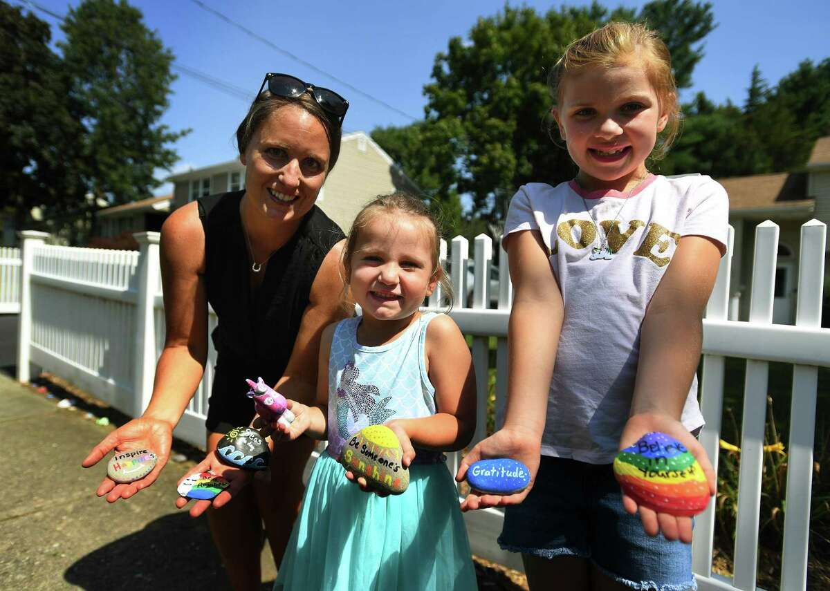 Krissy Futia and daughters Sienna, 3, and Isabella, 7, leave painted rocks with inspirational messages outside their home on Katona Drive in Fairfield, Conn. on Sunday, September 6, 2020. Futia and her daughters began the project at the beginning ov the Covid-19 pandemic.