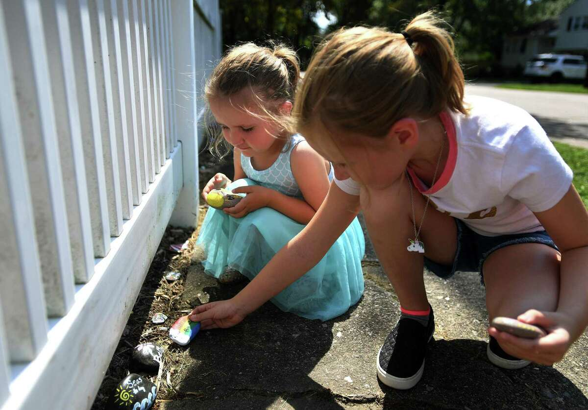 Sienna, 3, and Isabella Futia, 7, leave painted rocks with inspirational messages outside their home in Fairfield, Conn. on Sunday, September 6, 2020. Krissy Futia and her daughters began the project at the beginning ov the Covid-19 pandemic.