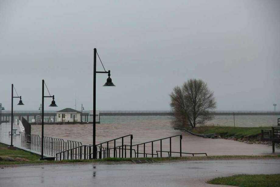 The Port Austin State Harbor flooding during a rainstorm in May. Despite the expected season decline in water levels, Lake Huron will still have above average water heights through the autumn. (Tribune File Photo)