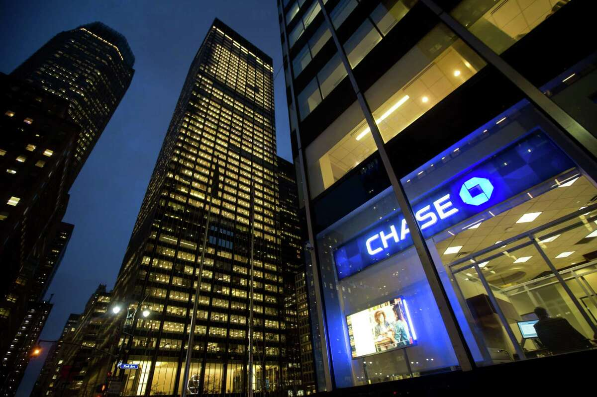 JPMorgan Chase & Co. signage is displayed at a bank branch, right, across from its Park Avenue headquarters, center, in New York on Jan. 12, 2016.