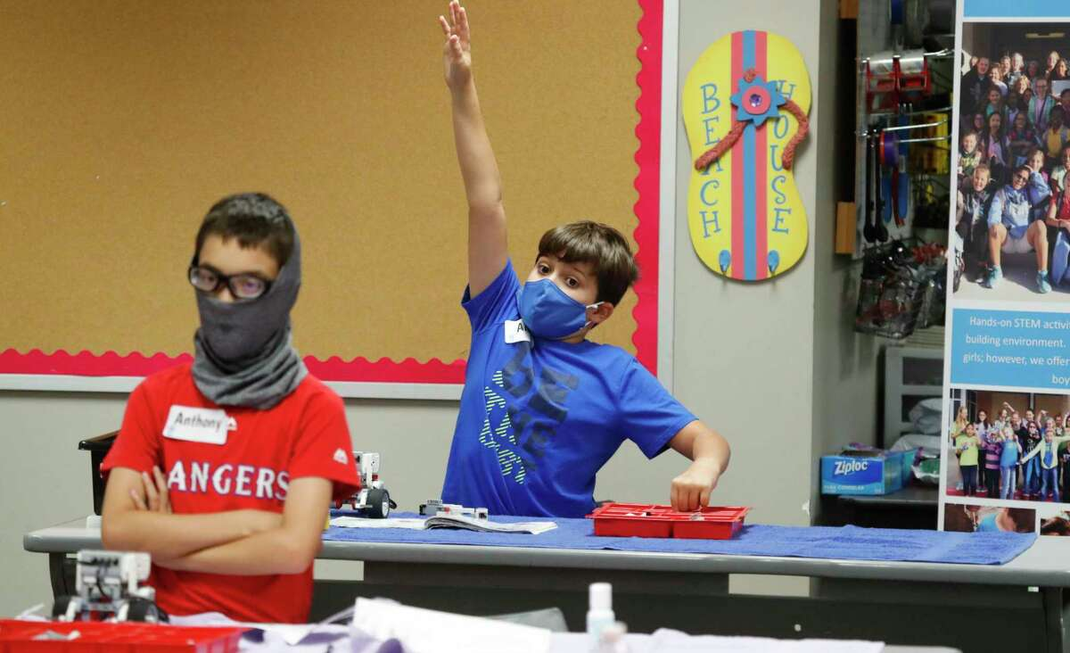 FILE - In this July 14, 2020, file photo, amid concerns of the spread of COVID-19, Aiden Trabucco, right, wears a mask as he raises his hand to answer a question behind Anthony Gonzales during a summer STEM camp at Wylie High School in Wylie, Texas. School districts that plan to reopen classrooms in the fall are wrestling with whether to require teachers and students to wear face masks - an issue that has divided urban and rural schools and yielded widely varying guidance. (AP Photo/LM Otero, File)