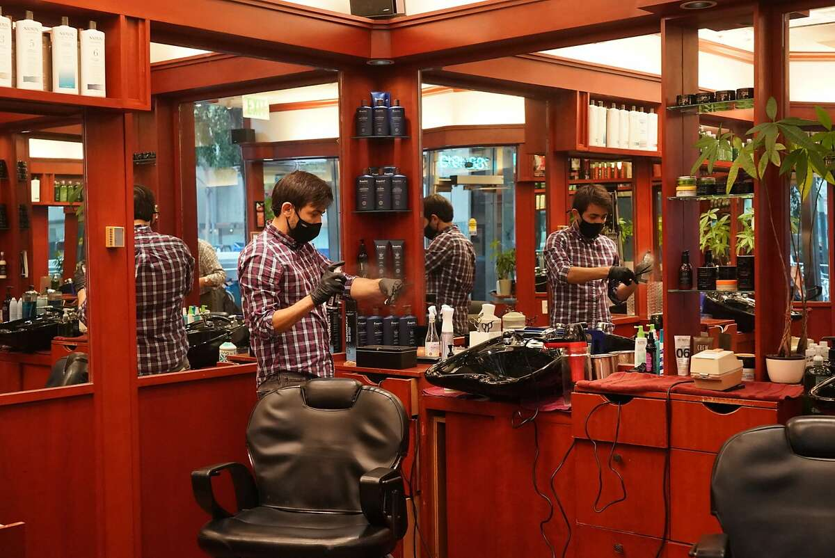 Iggy Ibrahimli prepares for customers at Ahmet's Barber & Hair Styling, 201 California St., for the first time since the mid-March shelter-in-place order, Monday, Sept. 14, 2020 in San Francisco, Calif. Other businesses now allowed to open are gyms, nail salons, massage and tattoo parlors, and hotels for indoor operations. Family entertainment, drive-in movies and tours may also open outdoors.