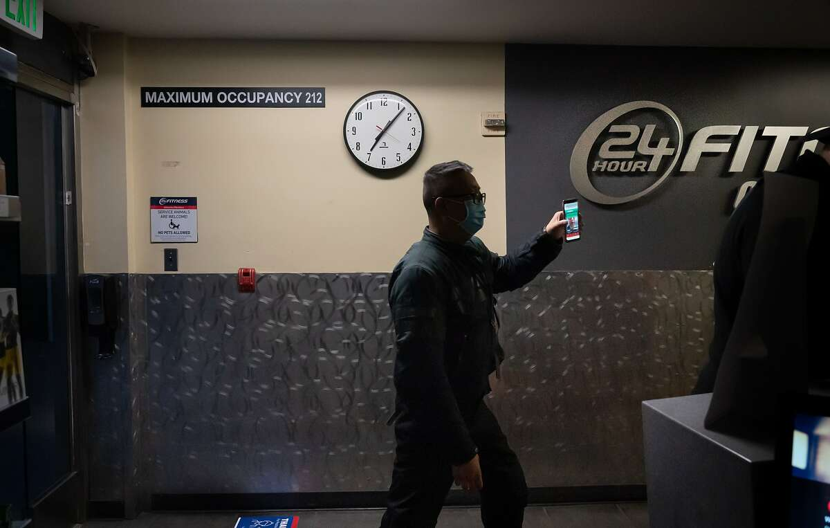 A member checks in for his reserved hour at the 24 Hour Fitness, 100 California St. It's opened for the first time since the mid-March shelter-in-place order on Monday, Sept. 14, 2020 in San Francisco, Calif. Other businesses now allowed to open are hair and nail salons, massage and tattoo parlors, and hotels for indoor operations. Family entertainment, drive-in movies and tours may also open outdoors.