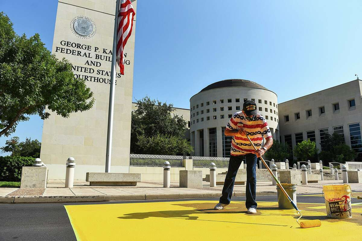 """Veterans and volunteers work to restore the """"Defund the Wall"""" mural on Saturday, Sept. 12."""