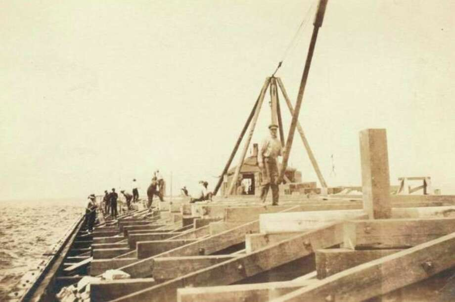 Workers are shown fixing the breakwater at the beach off Manistee Harbor in this photograph from the late 1800s. (Manistee County Historical Museum photo)