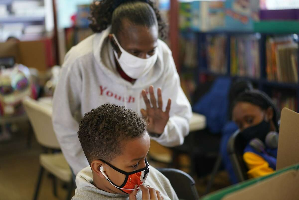Isaiah Howard , 9, is helped by Lisa Marie -Wiley as he attends a SF hub for kids for academic support and supervision - -a substitute for school at this point by a company called Youth 1st. on Monday, Sept. 14, 2020 in San Francisco, Calif.
