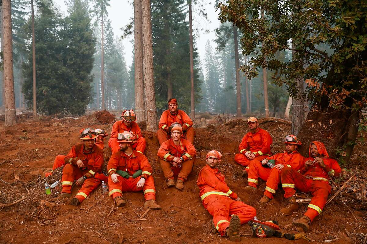 Valley View inmate firefighters take a break after cutting line on the North Complex Fire in Butte County, California on Sunday, Sept. 13, 2020.