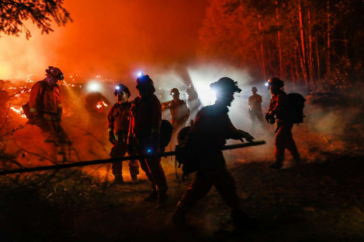 Valley View inmate firefighters cut down trees ahead of a backburn operation on the North Complex Fire in Butte County, California on Sunday, Sept. 13, 2020.