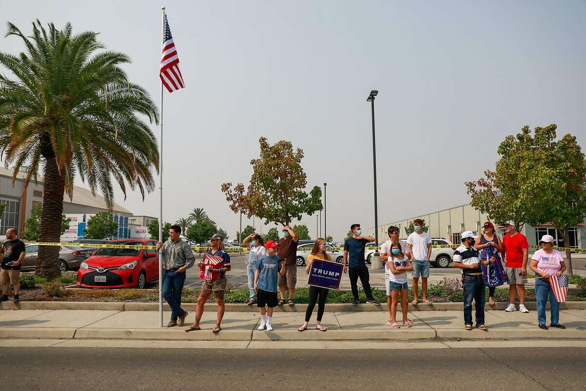 Trump supporters cheer on the street outside Sacramento McClellan Airport as President Donald Trump was being briefed on wildfires in a hangar in McClellan Park, Calif., Monday, Sept. 14, 2020.