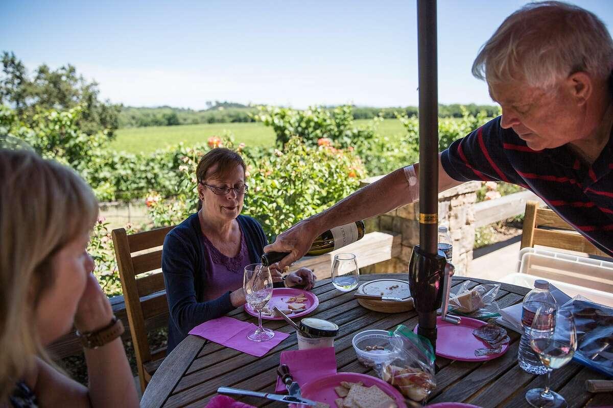 Gary Gronseth pours wine for Margot Burnham at Rochioli Vineyards in Healdsburg, California on July 5, 2017.