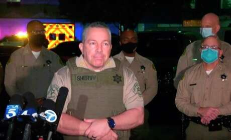 Los Angeles County Sheriff Alex Villanueva takes questions at a late-night news conference about the condition of two deputies shot in Compton, Calif. Authorities searched Sunday for a gunman who shot and wounded the deputies who were sitting in their squad car.