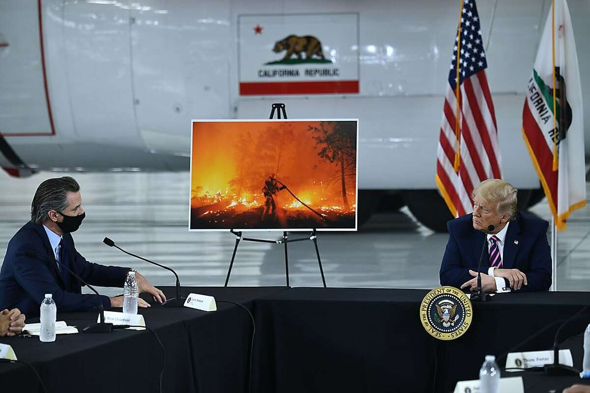 US President Donald Trump(R) speaks to California Governor Gavin Newsom(D-CA) at Sacramento McClellan Airport in McClellan Park, CA on Sept. 14, 2020 during a briefing on wildfires. (BRENDAN SMIALOWSKI/AFP via Getty Images/TNS)