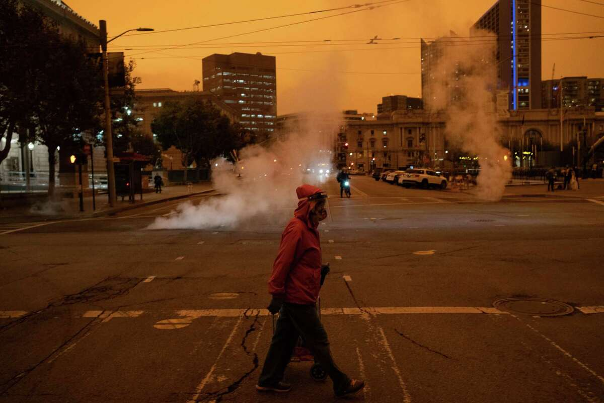A pedestrian crosses the street near City Hall on Wednesday as San Francisco was blanketed in an eerie haze from the wildfires. Photo by Nick Otto for The Washington Post