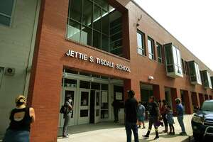 Parents wait outside Jettie S. Tisdale School to be distributed laptops for at home learning in Bridgeport, Conn. on Monday, September 14, 2020.