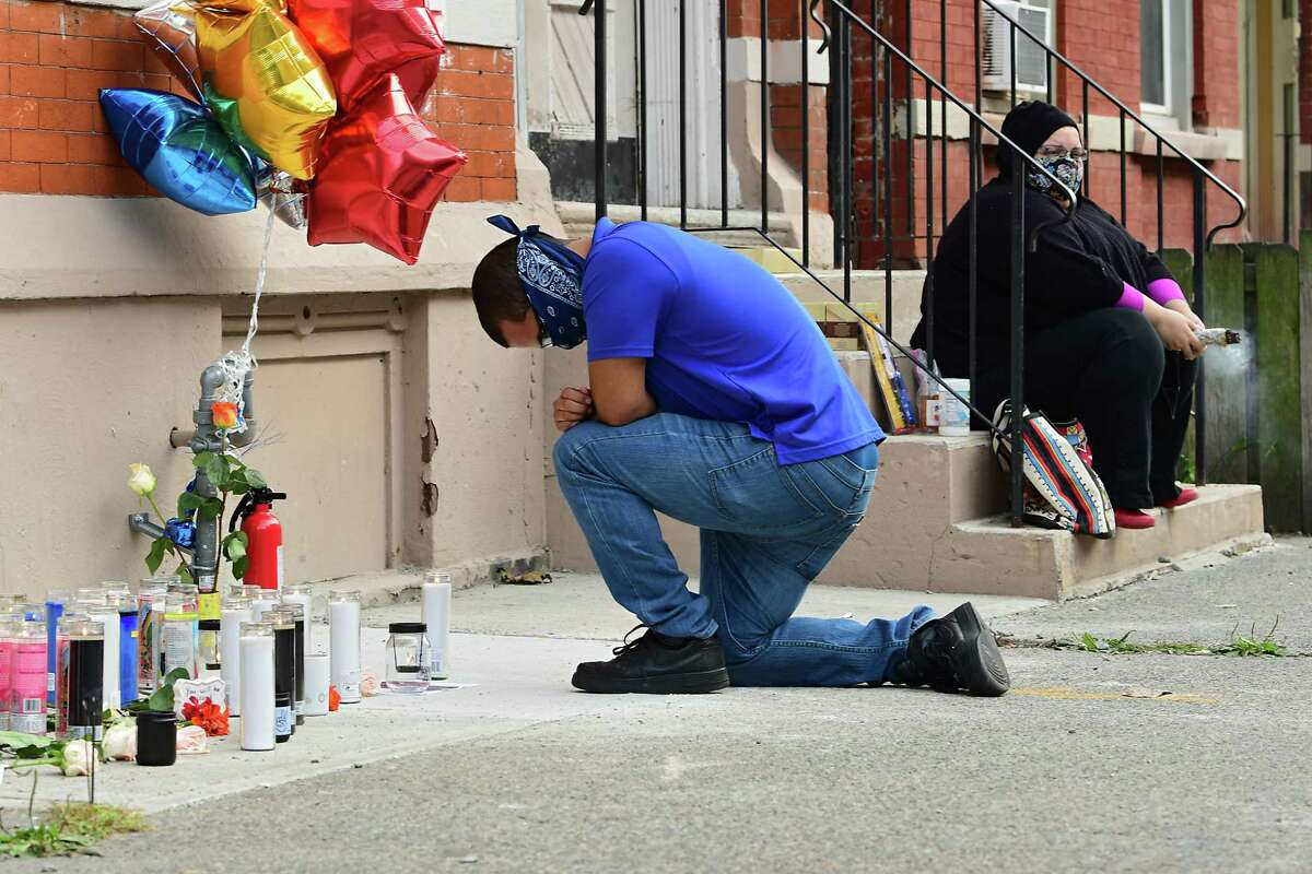 A man kneels by a memorial as Equality for Troy holds a vigil on Old Sixth Avenue to honor Ayshawn Davis, the 11-year-old boy shot and killed late Sunday on Monday, Sept. 14, 2020 in Troy, N.Y. People also called for an end to violence. (Lori Van Buren/Times Union)