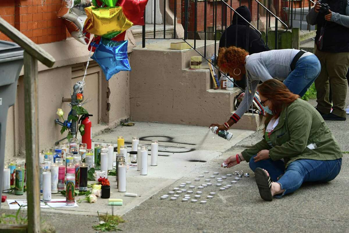 A woman sprays paint with a R.I.P. message as another woman arranges candles in initials as Equality for Troy holds a vigil on Old Sixth Avenue to honor Ayshawn Davis, the 11-year-old boy shot and killed late Sunday on Monday, Sept. 14, 2020 in Troy, N.Y. People also called for an end to violence. (Lori Van Buren/Times Union)