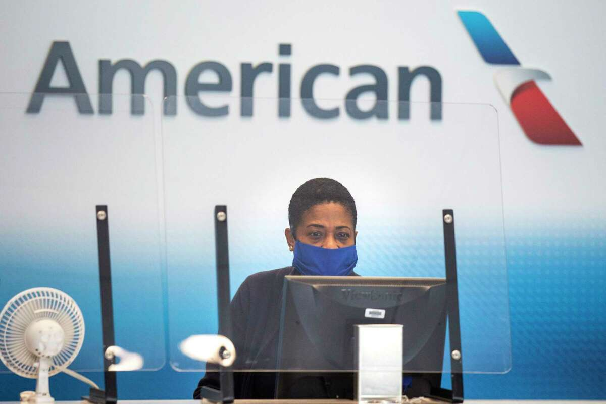 An American Airlines employee waits to help the next passenger check luggage in Terminal A at DFW International Airport in Irving, Texas, on Sunday, July 26, 2020. American is one of the major airlines that have eliminated fees for changing your flight plans. Their aim is to win over passengers who still concerned about air travel. (Lynda M. Gonzalez/The Dallas Morning News/TNS)