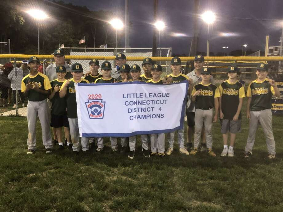 Members of the Hamden 12U Little League baseball team hold up the championship banner after winning the District 4 championship on Monday night. Photo: Will Aldam / Hearst Connecticut Media
