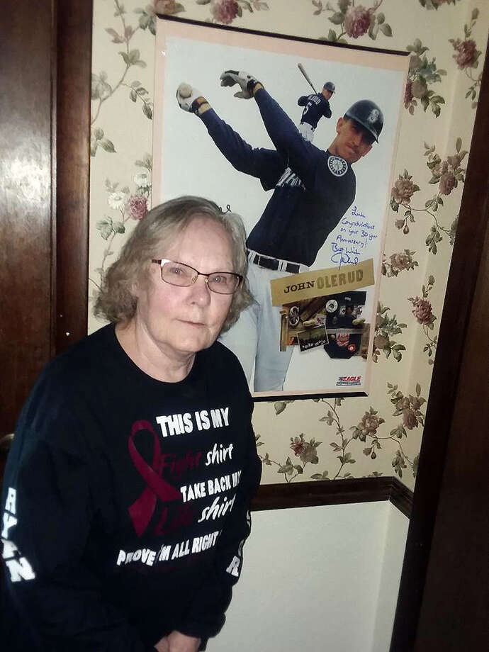 Linda Kovarik poses with her autographed poster of former Seattle Mariner John Olerud, who had an aneurysm within 30 days of Linda's in 1989. The Kovariks and Oleruds are part of a brain aneurysm support group on social media. Photo: Courtesy Of The Kovarik Family