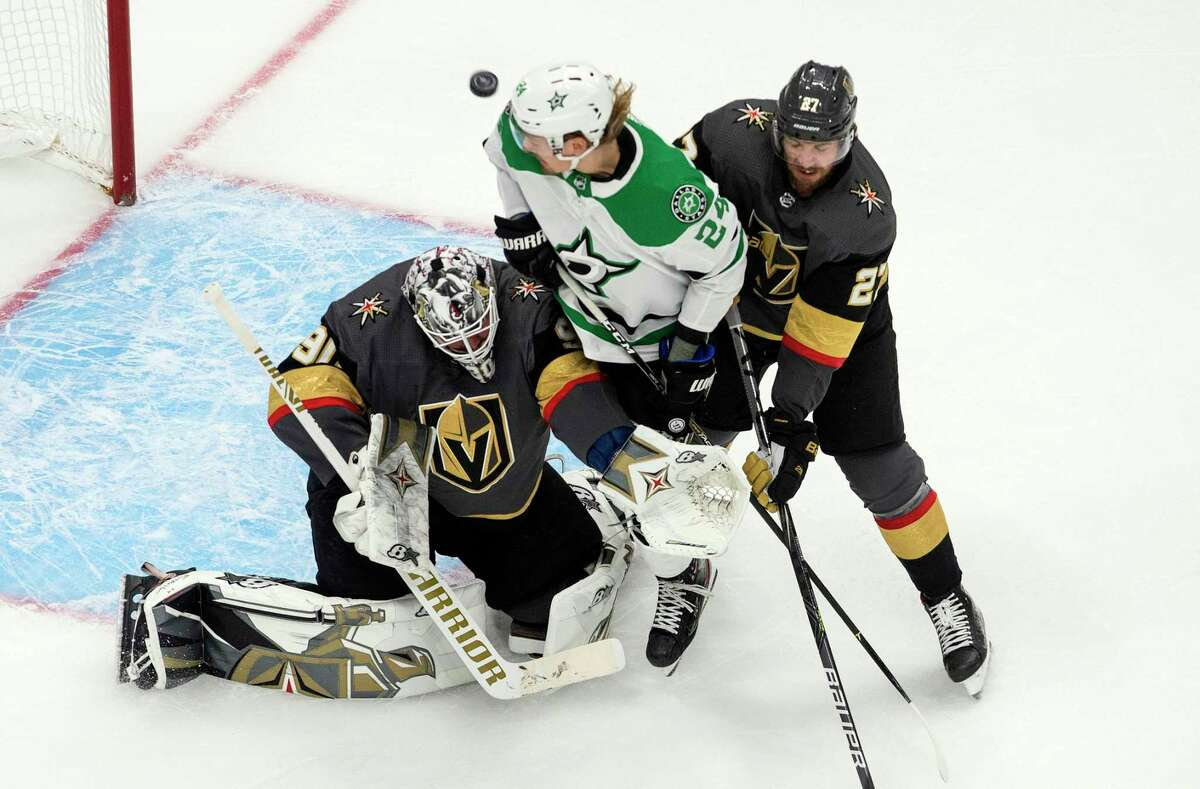 Dallas Stars' Roope Hintz (24) and Vegas Golden Knights' Shea Theodore (27) battle as Golden Knights goalie Robin Lehner (90) makes a save during first-period NHL Western Conference final playoff game action in Edmonton, Alberta, Monday, Sept. 14, 2020. (Jason Franson/The Canadian Press via AP)