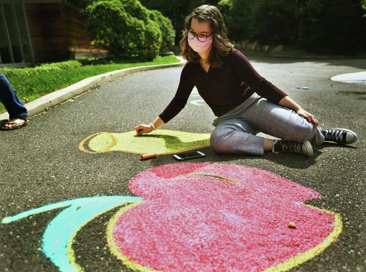 Ariel Langberg, 16, of Ridgefield, uses chalk to draw an apple and pot of honey, symbols of Rosh Hashana, outside the entrance of Temple B'Nai Chaim. The chalk drawing was the inaugural event of the temple's youth group, kicking off the High Holy Days.