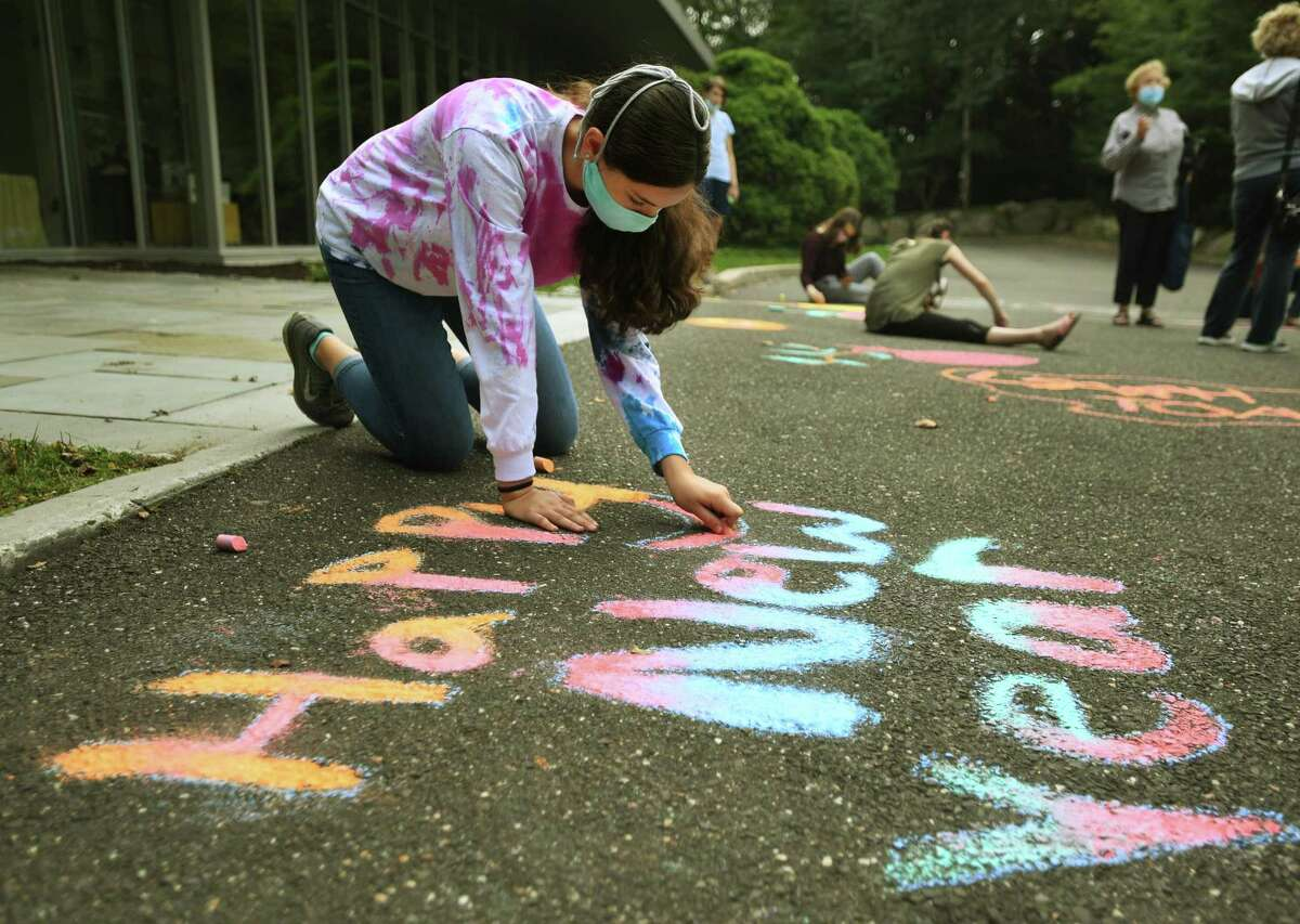 Nina Saunders, 14, of Bethel, and members of the Temple B'Nai Chaim youth group, use chalk to decorate the entrance to the synagogue for the High Holy Days in Georgetown on Sunday, Sept. 13.